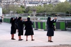 Nuns taking photos Eiffel Tower at dusk