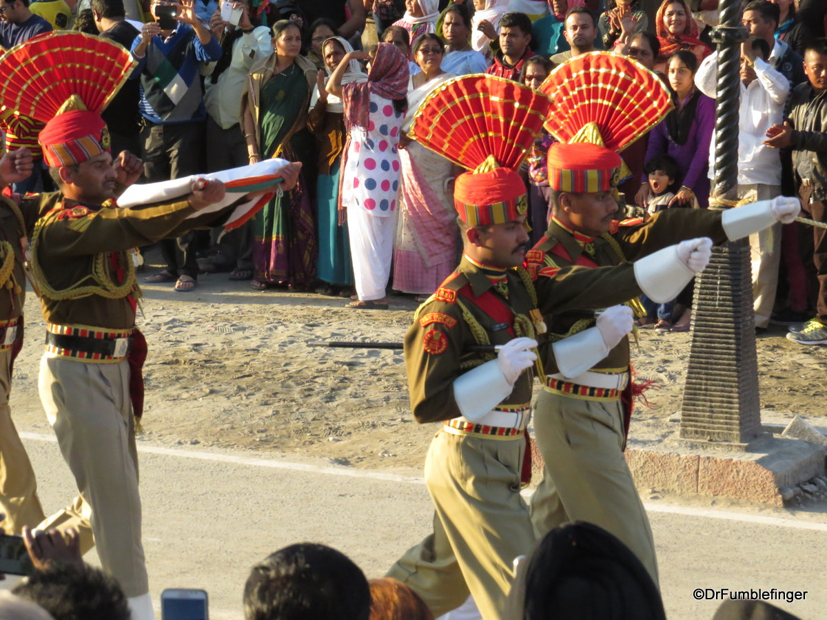 Uniformed guards carrying flag at Wagah Border crossing